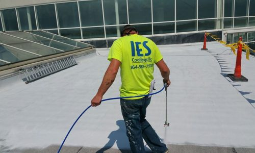 Man coating roof on commercial building