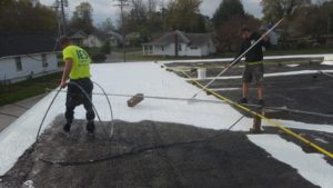 Man coating Commercial Roof.