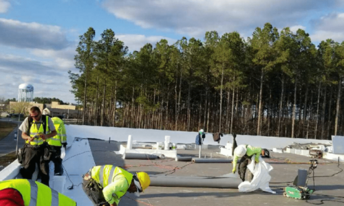 Roofing technicians working on a commercial roof and building.